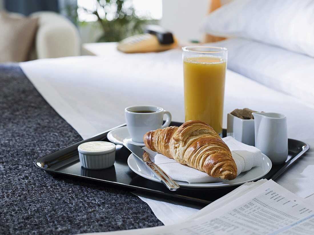 A breakfast tray on a hotel bed