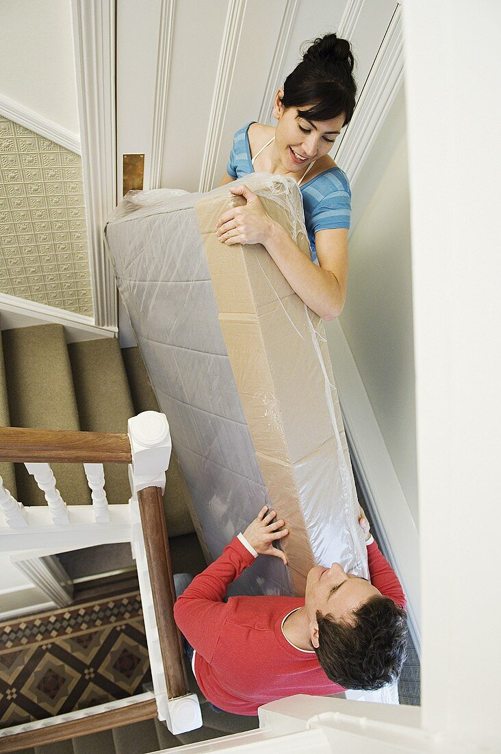 A couple carrying mattress upstairs
