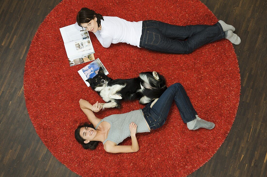 A women and a dog lying on a rug