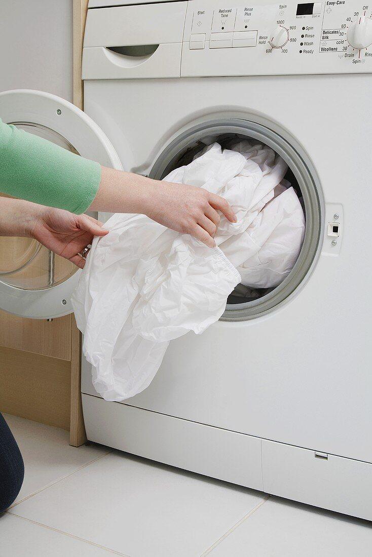 A woman taking a sheet out of a washing machine