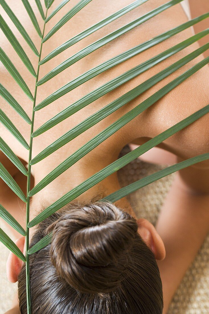 Girl with palm leaf on her back