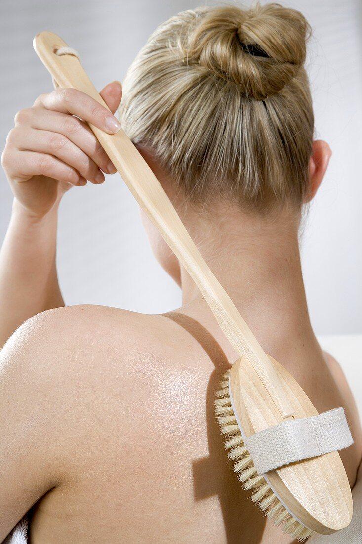 Back massage with long-handled bath brush