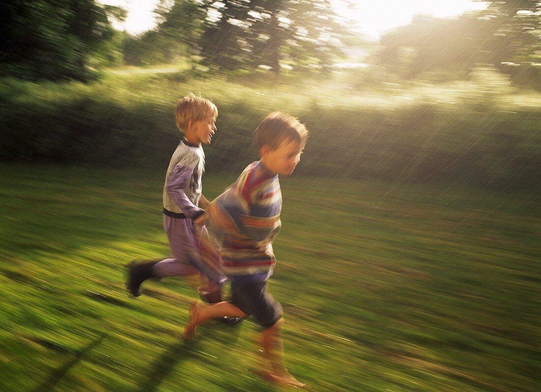 Two little boys running across a field in the rain