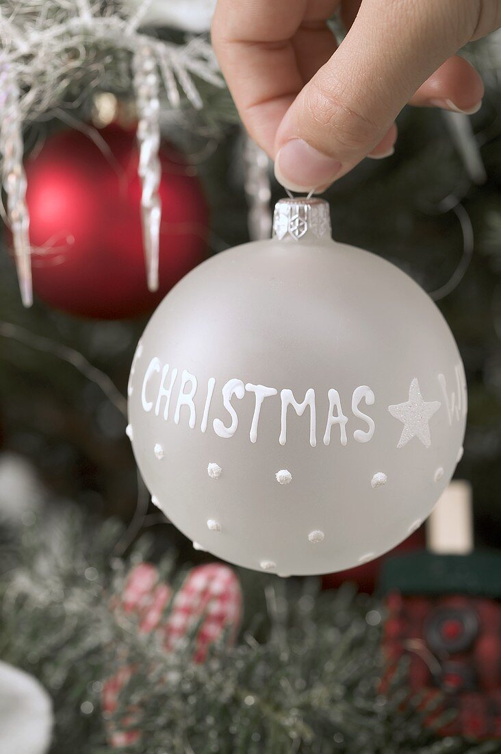 Hand holding white Christmas bauble