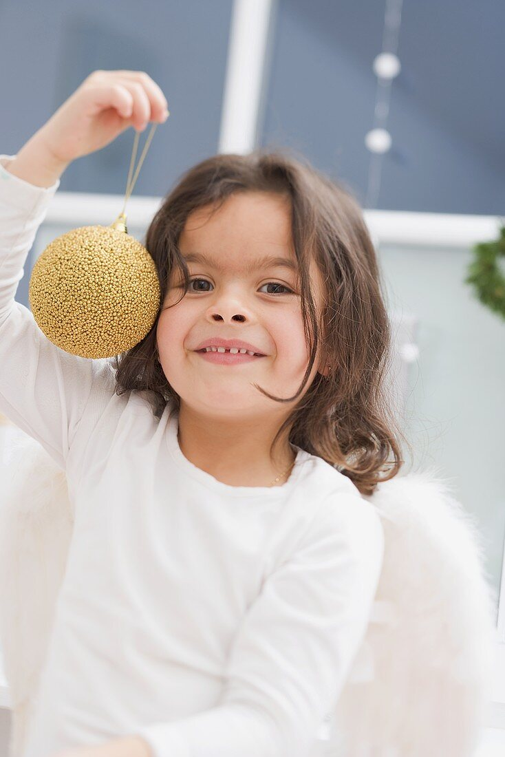 Small girl holding gold Christmas bauble