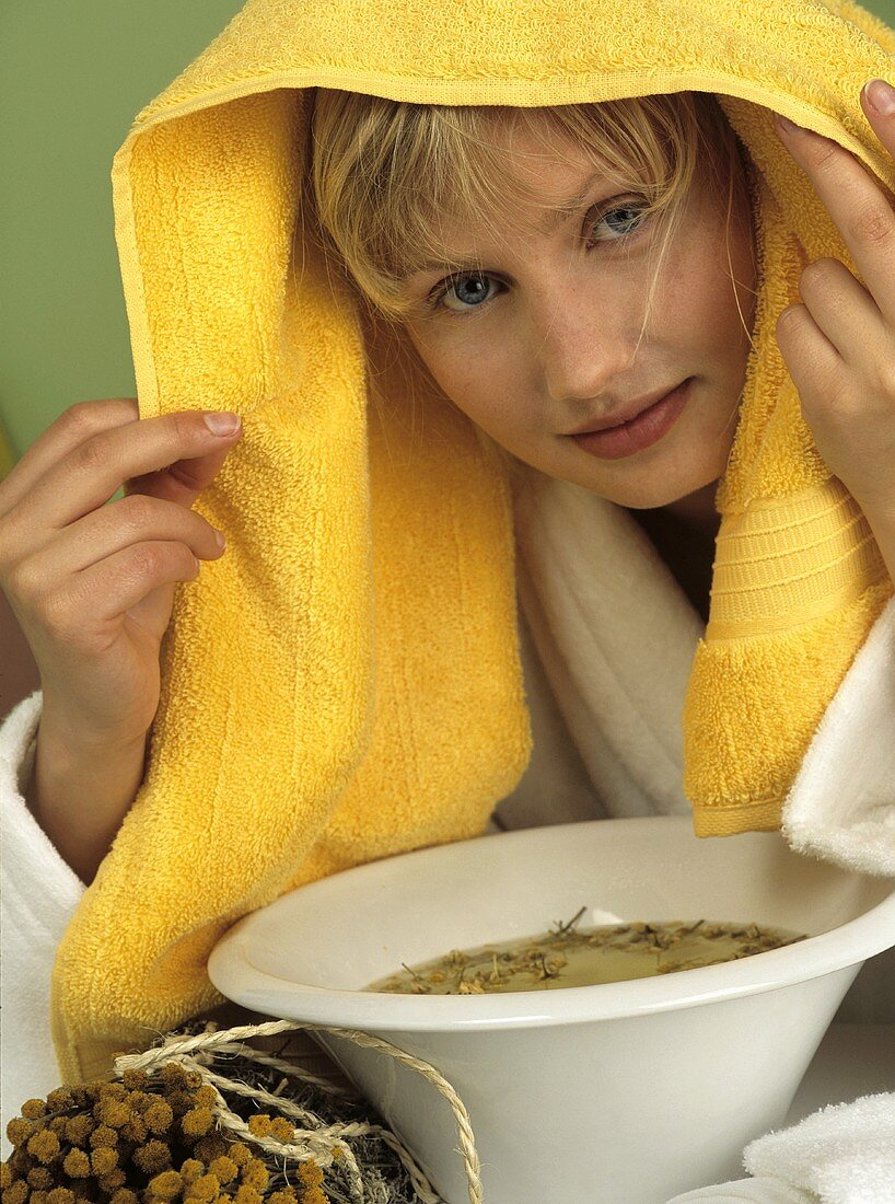 Young woman taking a chamomile steam bath