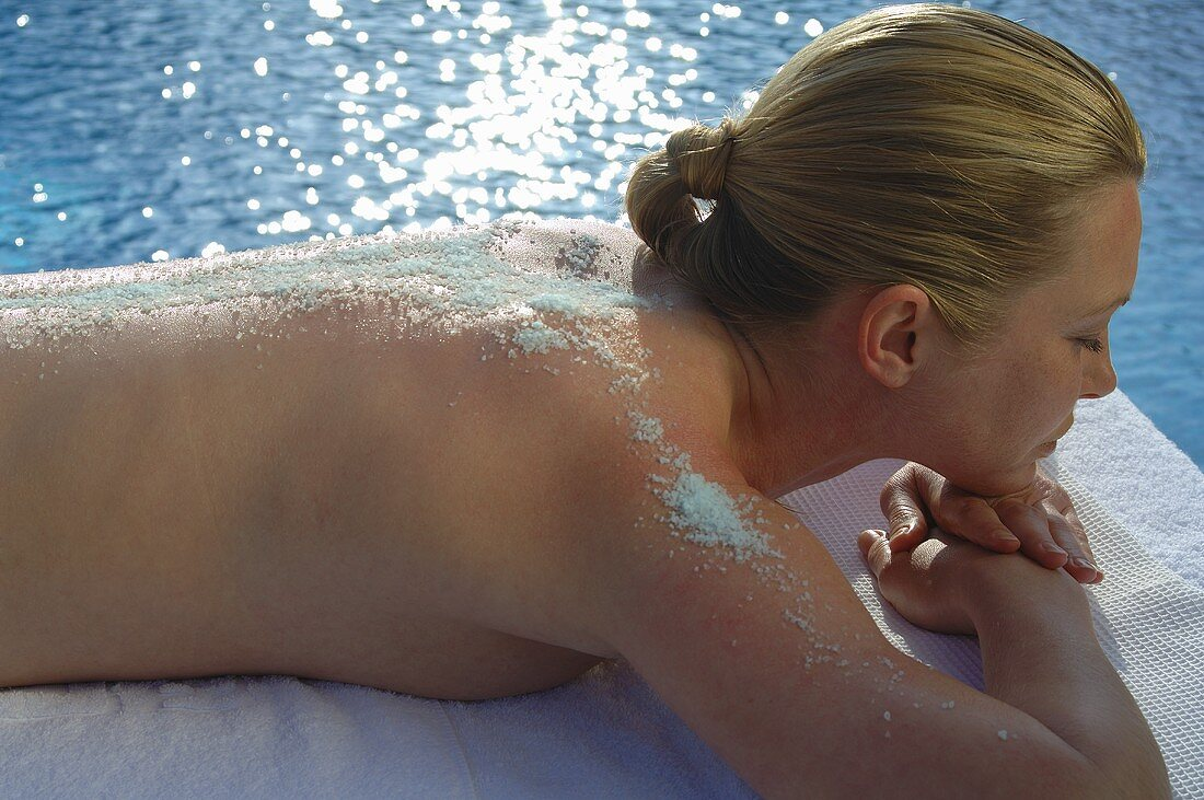 Woman with exfoliating scrub on her back lying by pool