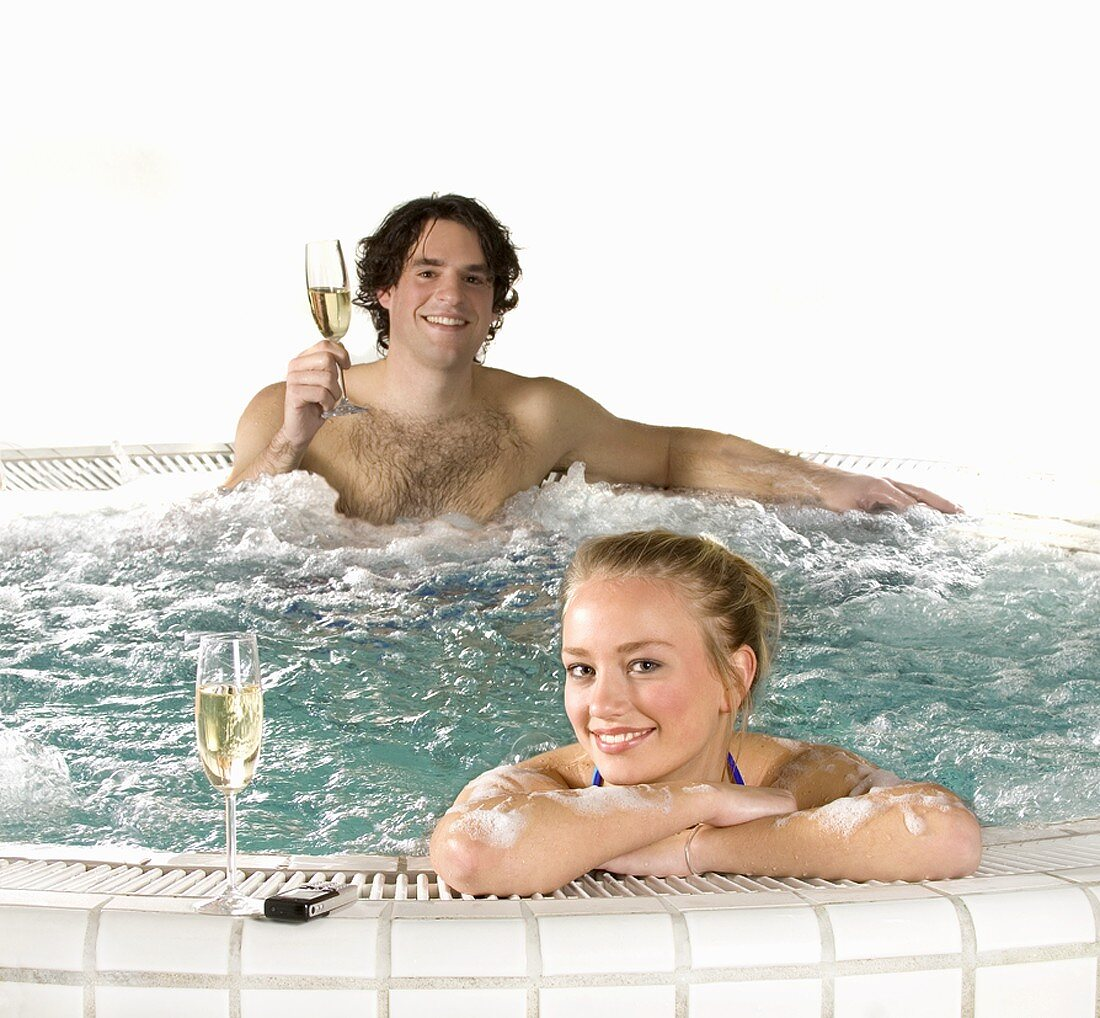 Young couple with sparkling wine in whirlpool