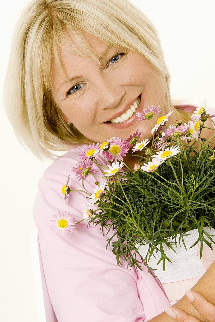 Woman with pot of marguerites in her hands