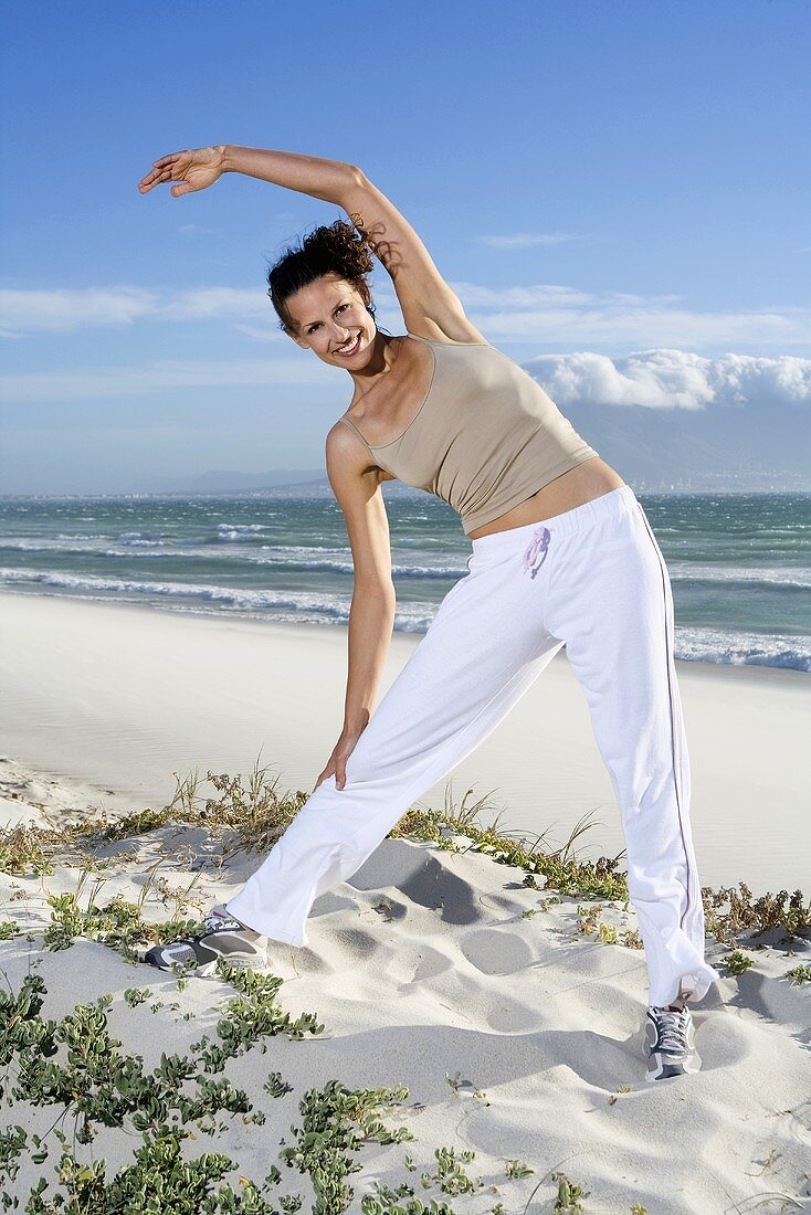 South Africa, Cape Town, Young woman stretching on beach