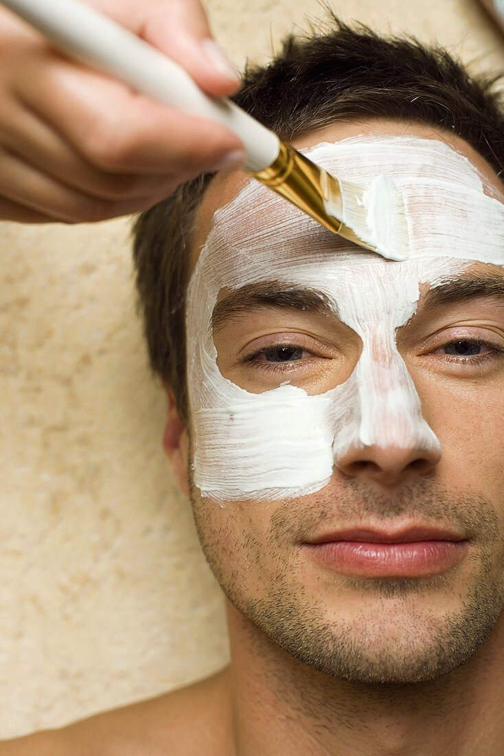 Man having a facial (facial mask being applied)