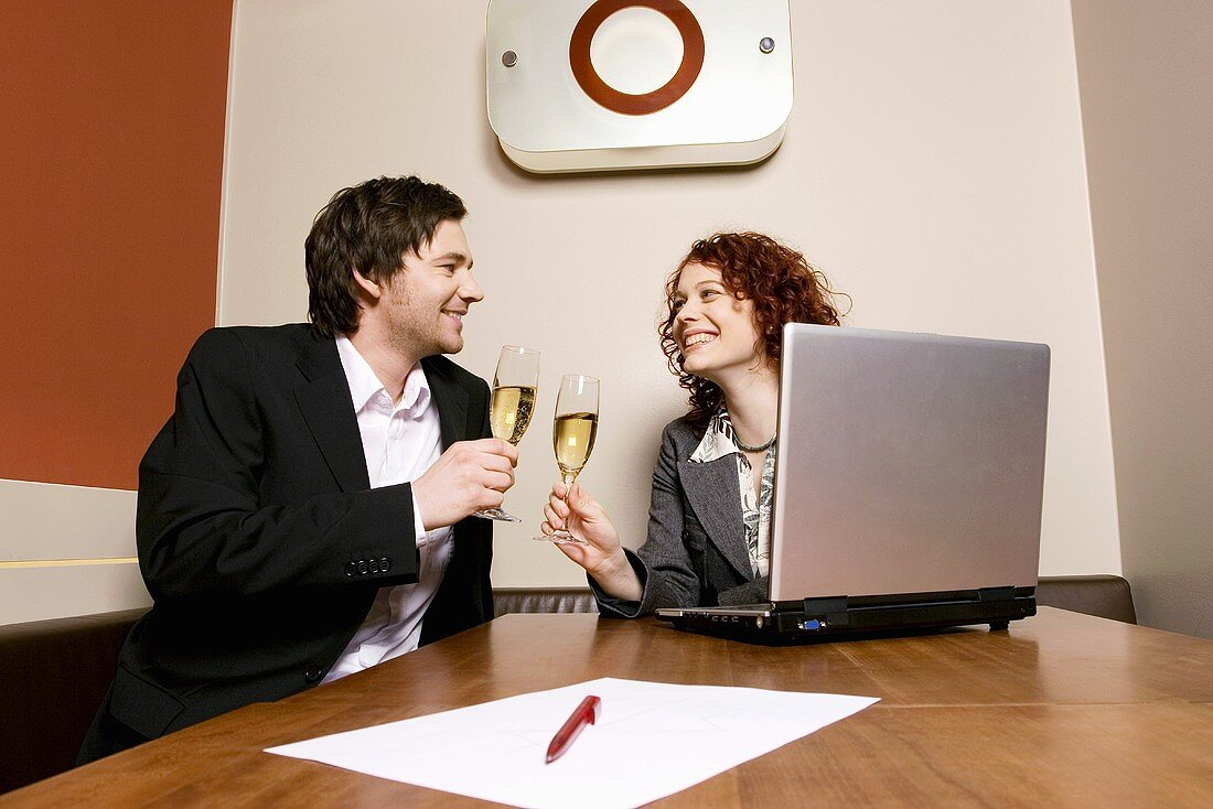 Couple drinking champagne in office