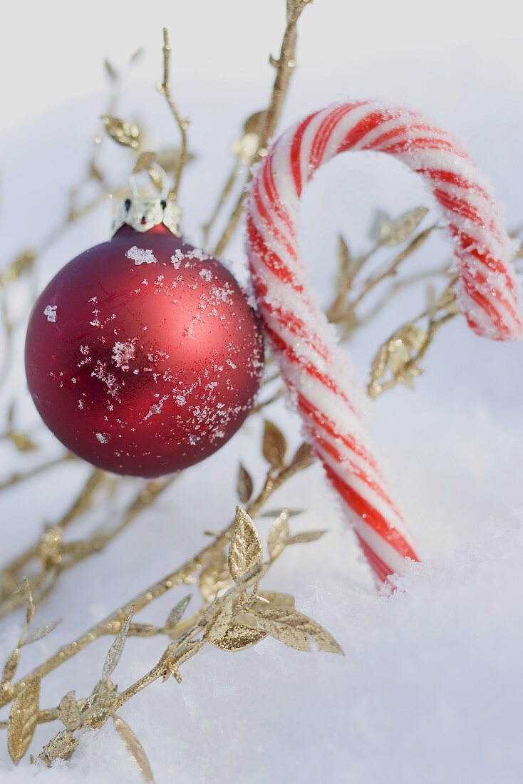 Christmas bauble and candy cane in snow