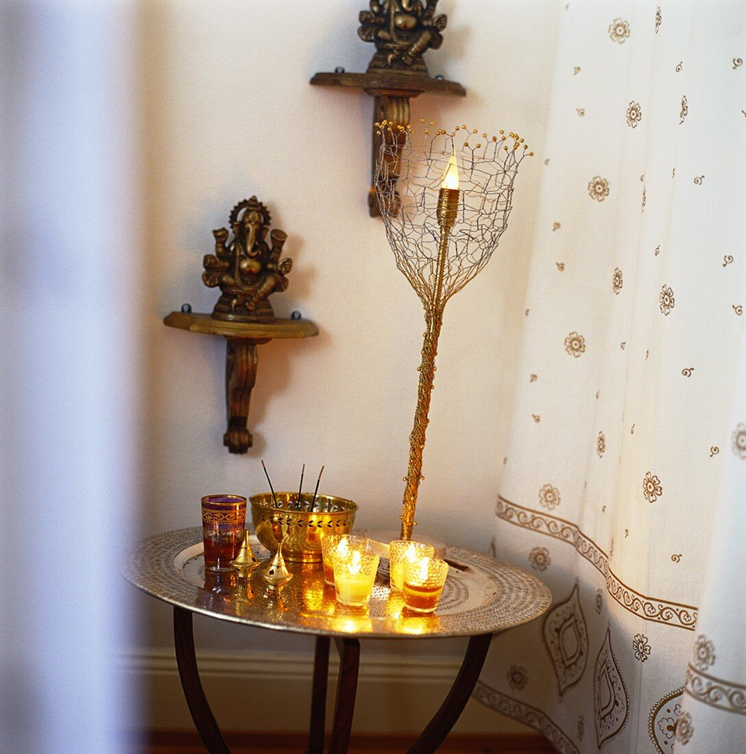 Windlights and incense sticks on round table