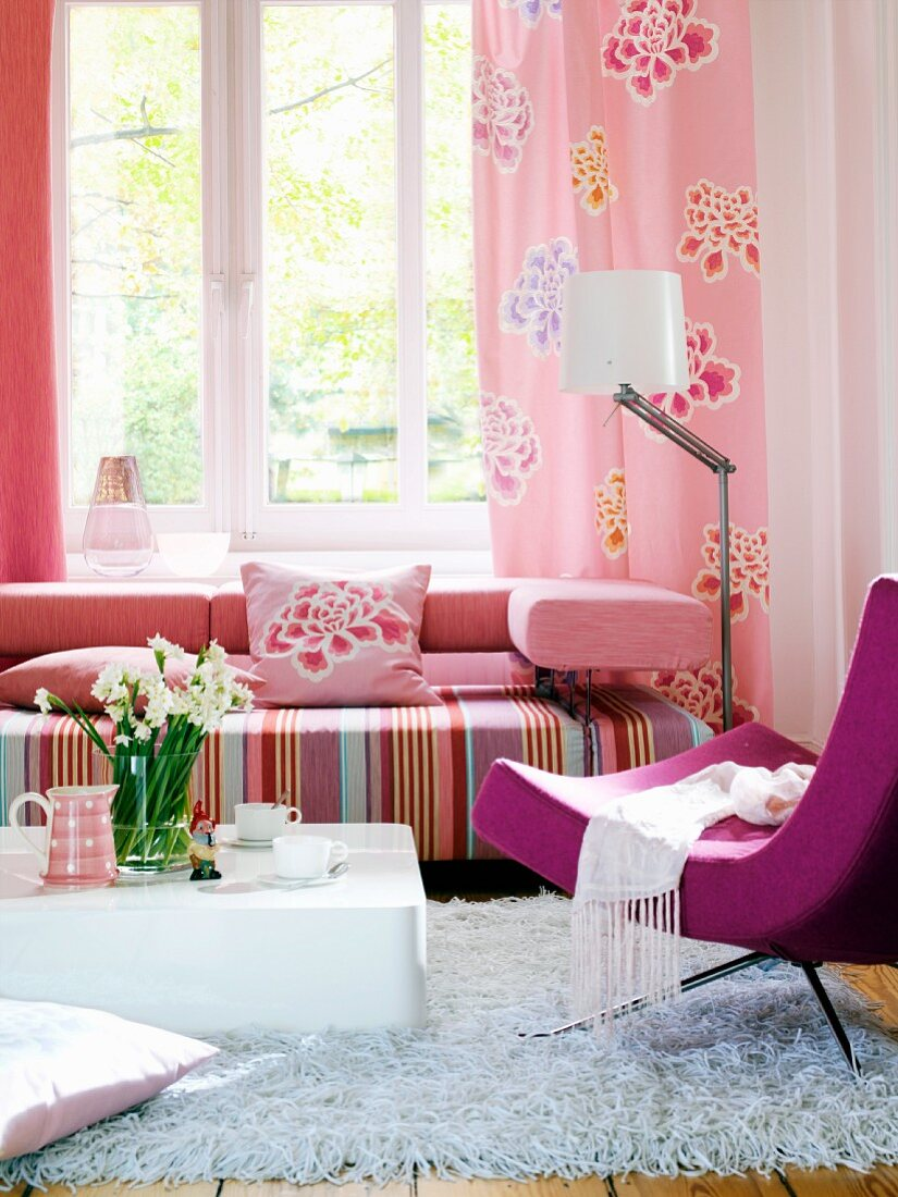 Living room with couch in shades of pink below window; designer armchair and coffee table