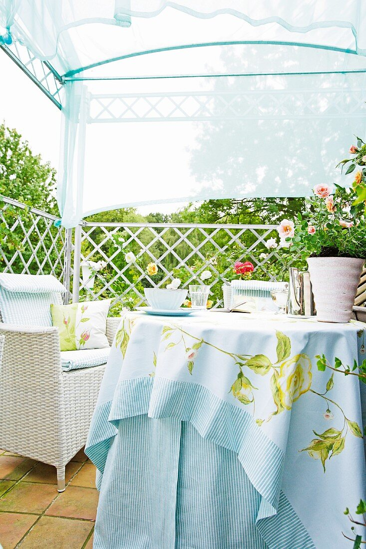 Balcony with round table, wicker armchair, roses and blue canopy