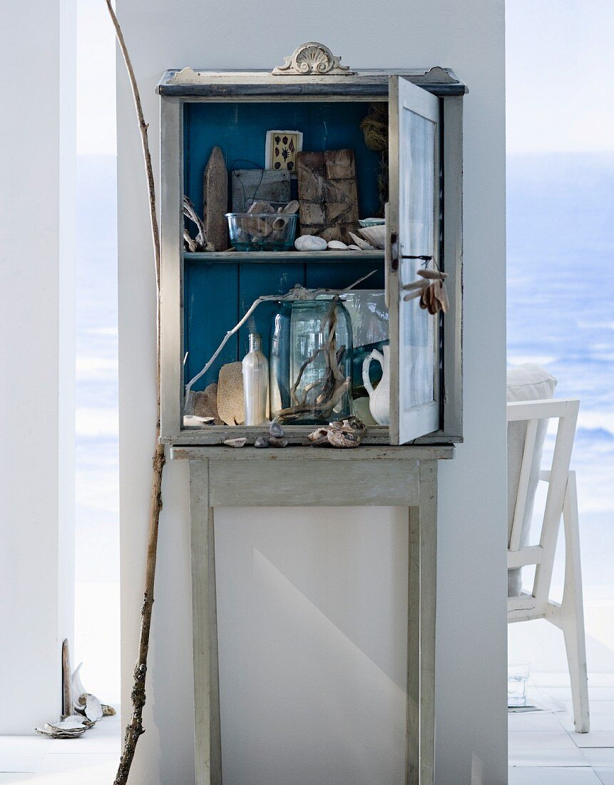 An old wooden cabinet filled with things found on the beach