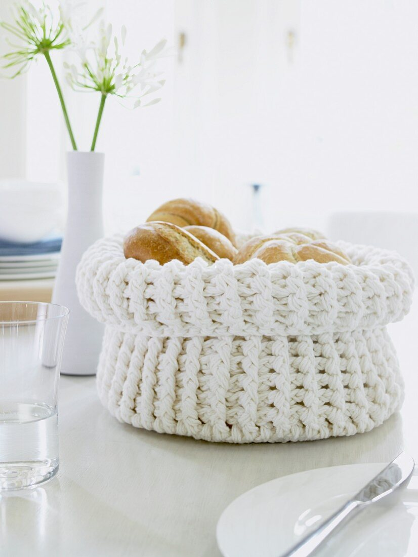 A white crochet bread basket filled with fresh rolls