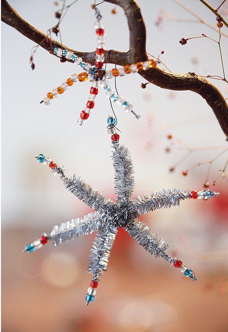 Selbst gebastelte Weihnachtssterne aus Perlen auf einem Ast