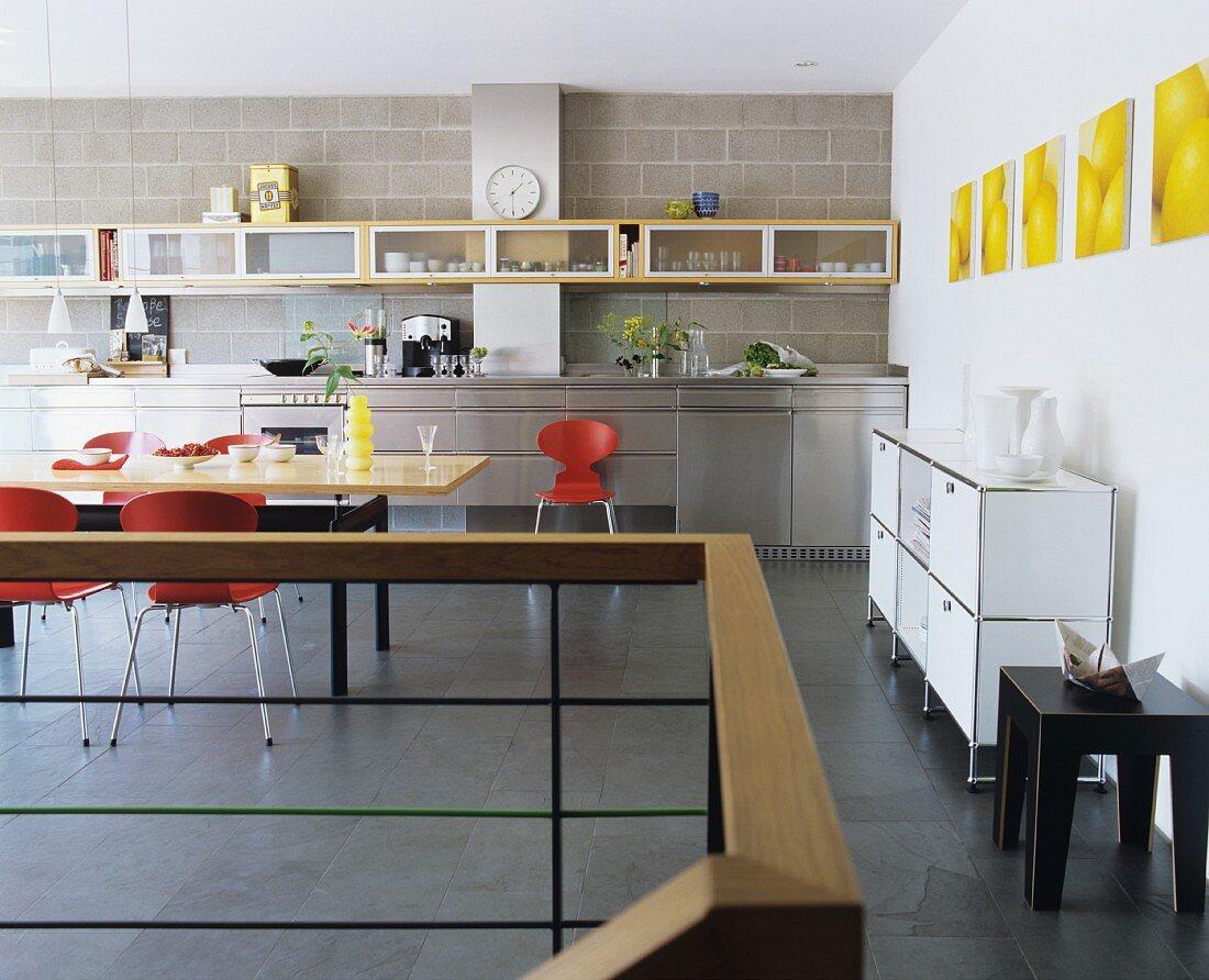 Grosszügige moderne Küche mit Edelstahl-Küchezeile sowie Wandregal und Esstisch aus Ahornholz