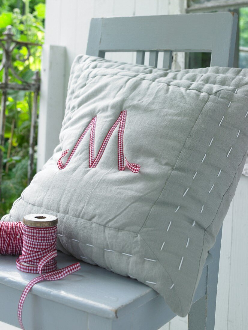 A homemade decorative cushion with an appliquéd letter