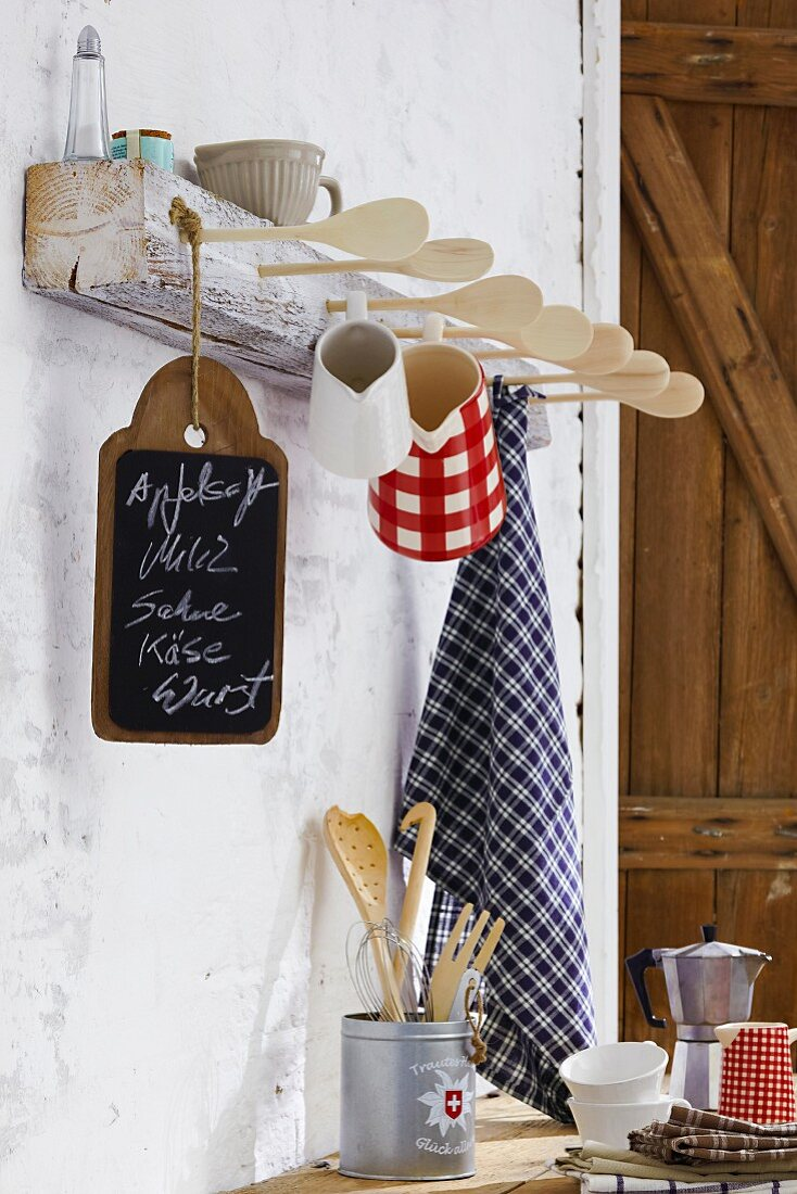 Hand-crafted rack with tea towels, cups & jugs hanging from wooden spoons