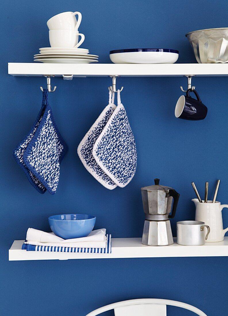 Kitchen utensils on white shelves on blue wall