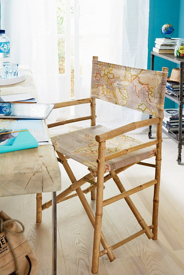 A director's chair with a map print in front of a deck