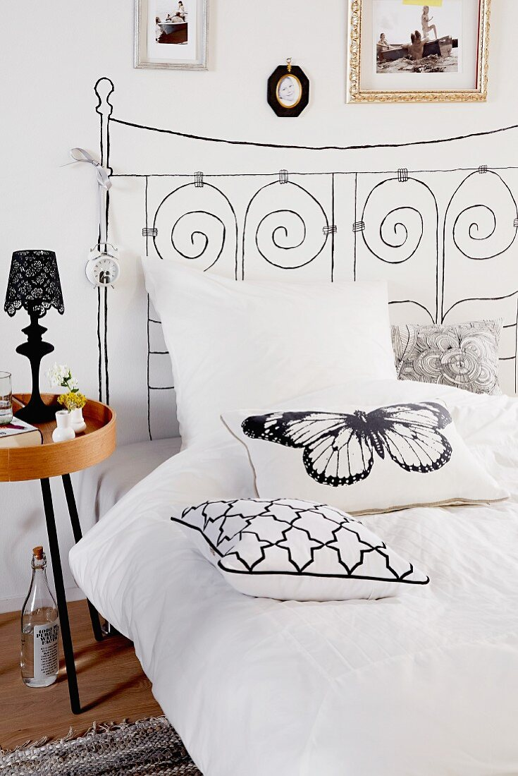 Bed with headboard painted on wall & scatter cushions