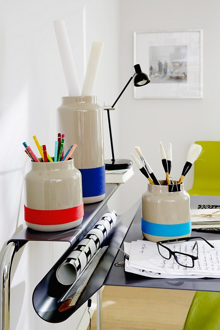 Plain grey vases decorated with stripes and used to store office supplies