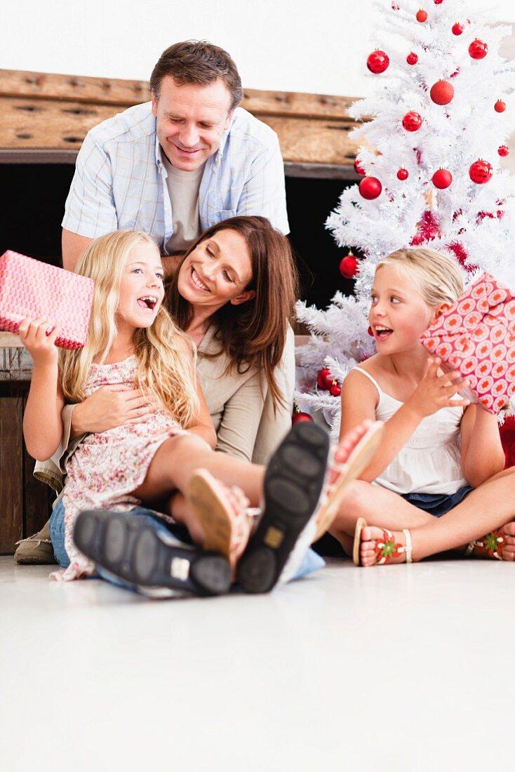 Familie mit Geschenken beim Christbaum