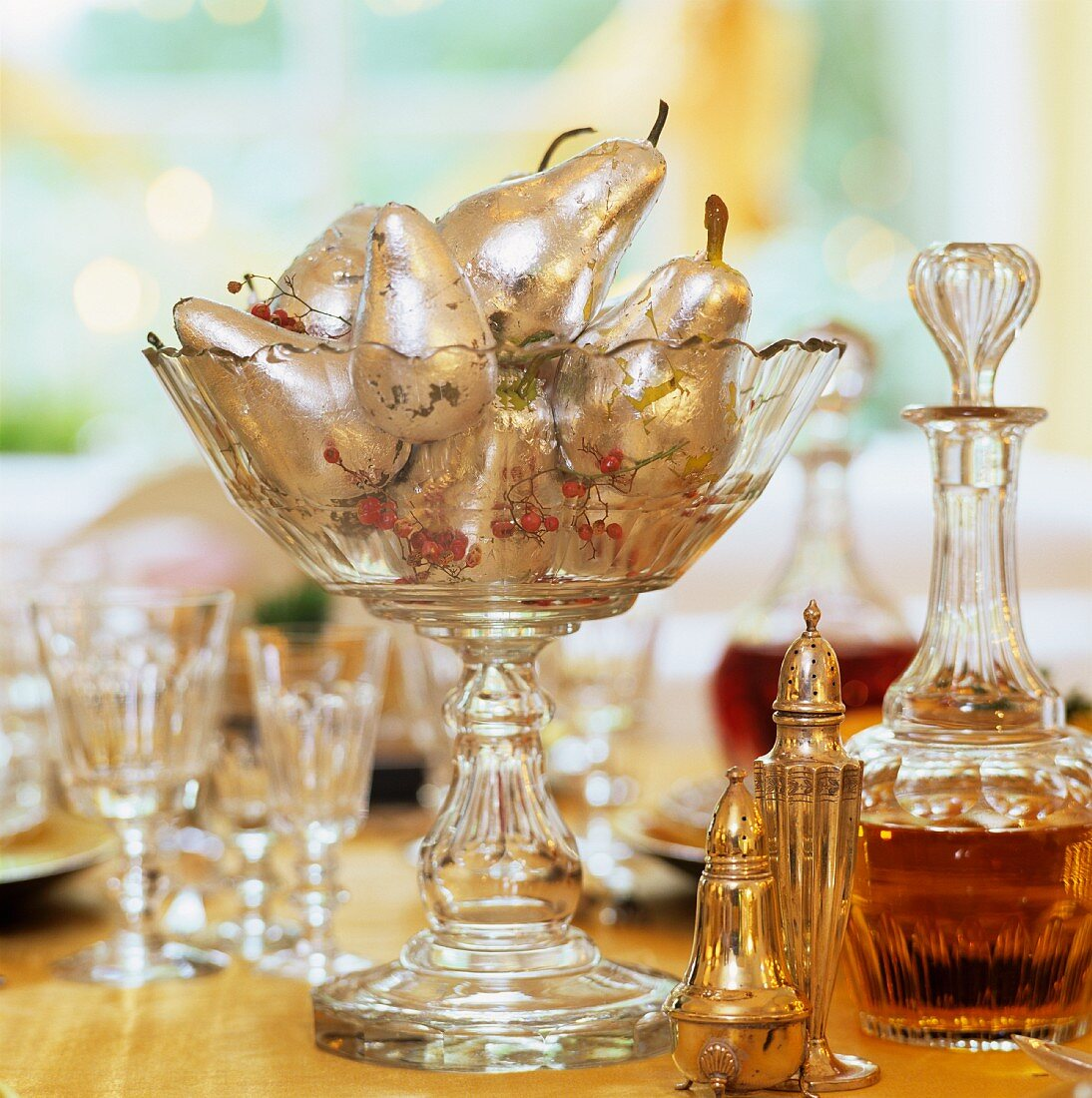 Silver ornamental pears in glass goblet next to crystal decanter and silver cruet