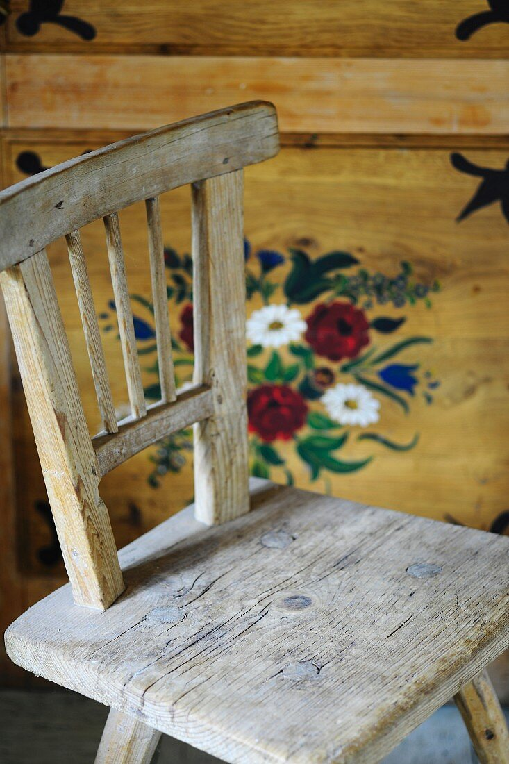 Rustic chair in front of painted farmhouse cupboard