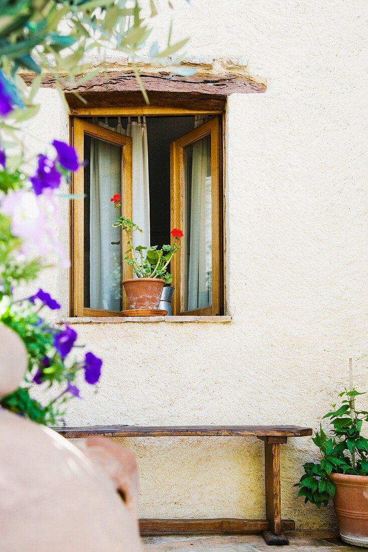 Eine Holzbank an der Hauswand unter dem geöffneten Fenster mit Geranie