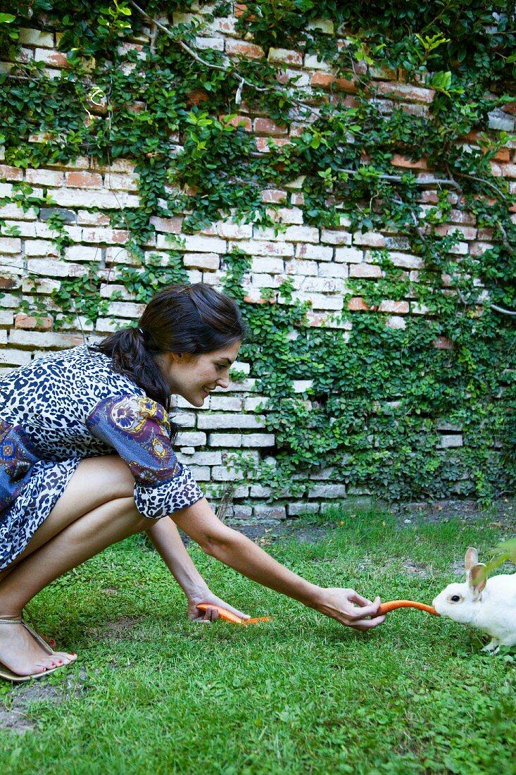 Woman feeding carrots to a rabbit