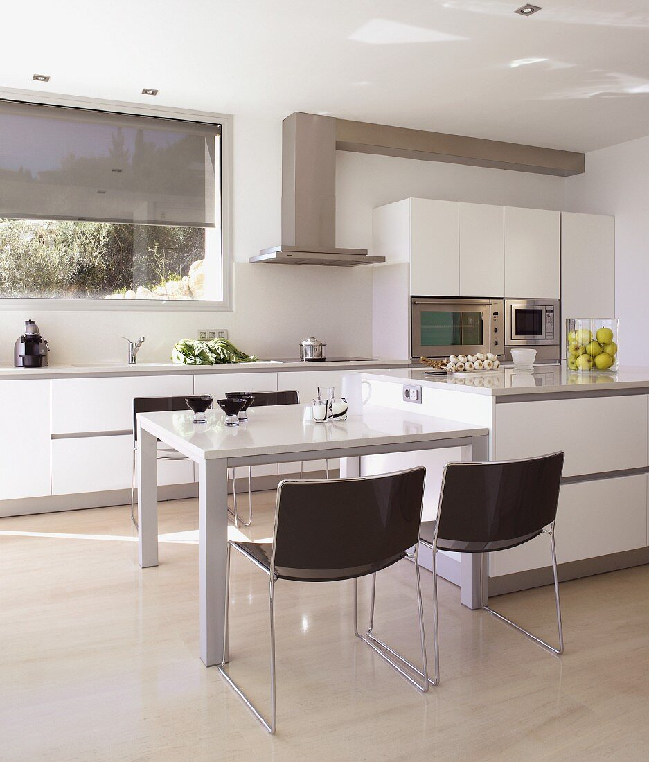 Open-plan kitchen with dining area next to base unit island; window with half-open blind and extractor hood in background