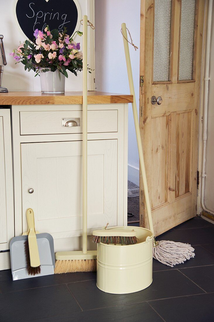 Cleaning utensils in front of country house style kitchen unit