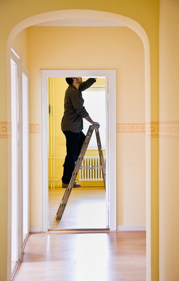 Man changing a light-bulb on a ladder