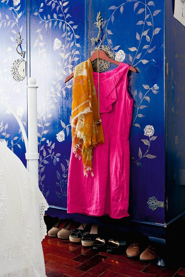 Hot pink dress and scarf on coat hanger hanging on door handle of blue wardrobe with pale floral pattern