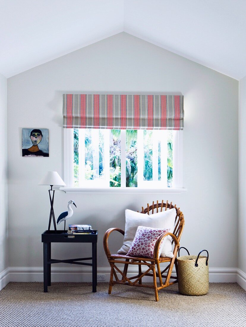Cozy bamboo chair with adjoining tray table under window with striped roller blind