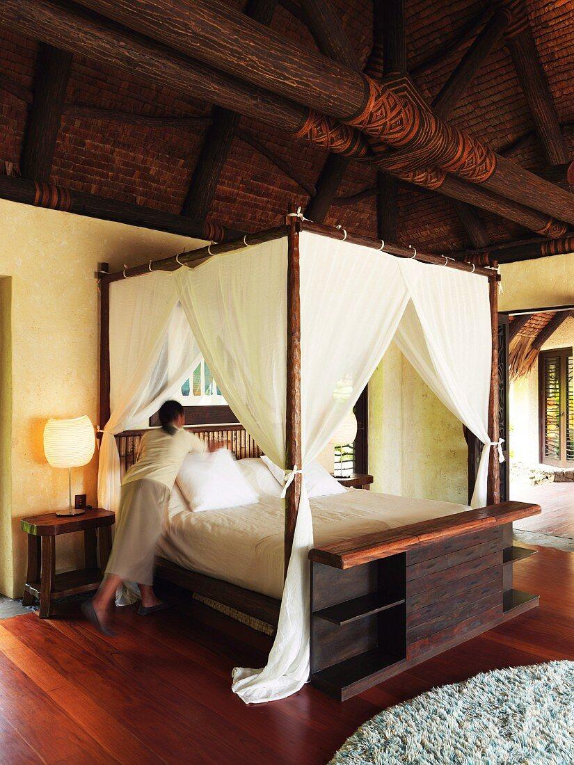 Chambermaid making bed in elegant, Oriental wooden house