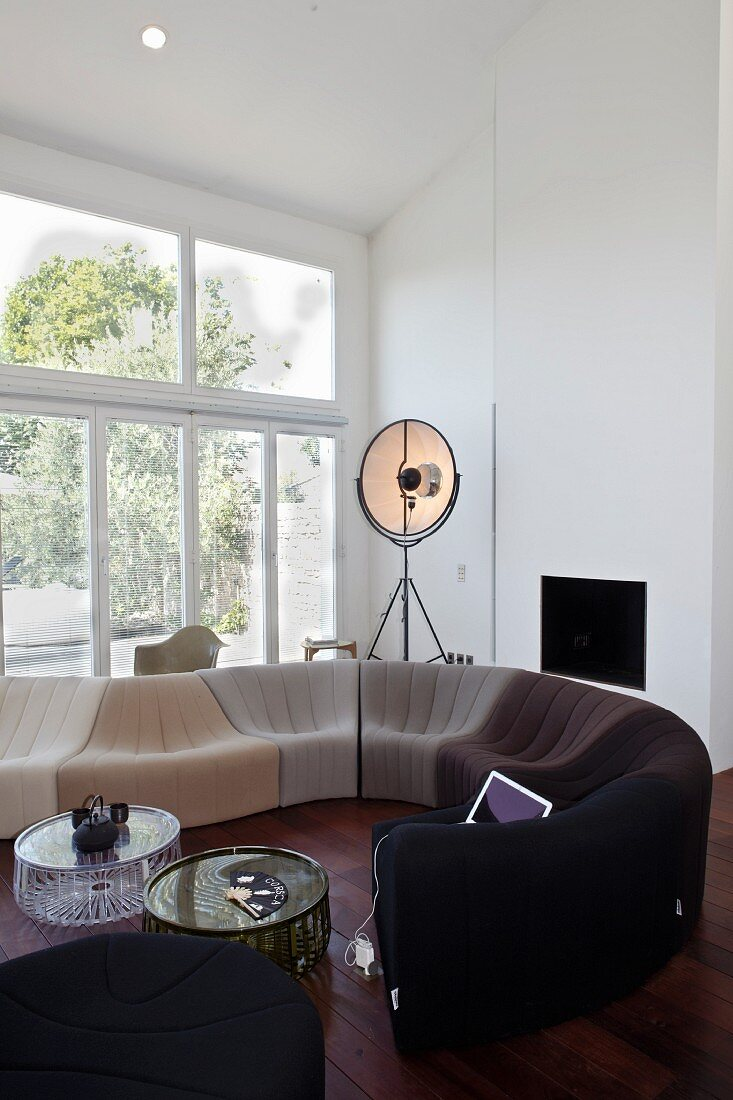 Contemporary sofa combo in front of a large bank of windows in a living room with dark wood flooring and pitched ceiling