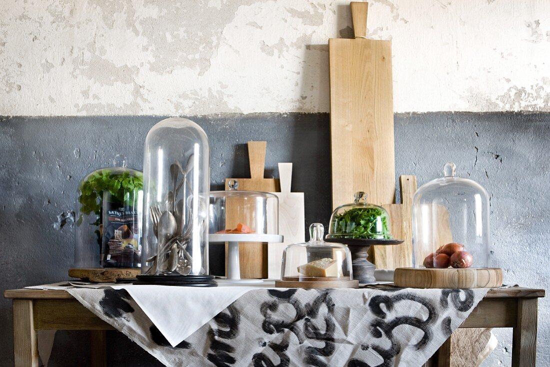 Tisch mit an der Wand lehnenden Schneidebrettern und Lebensmitteln und Küchenutensilien unter Glasglocken