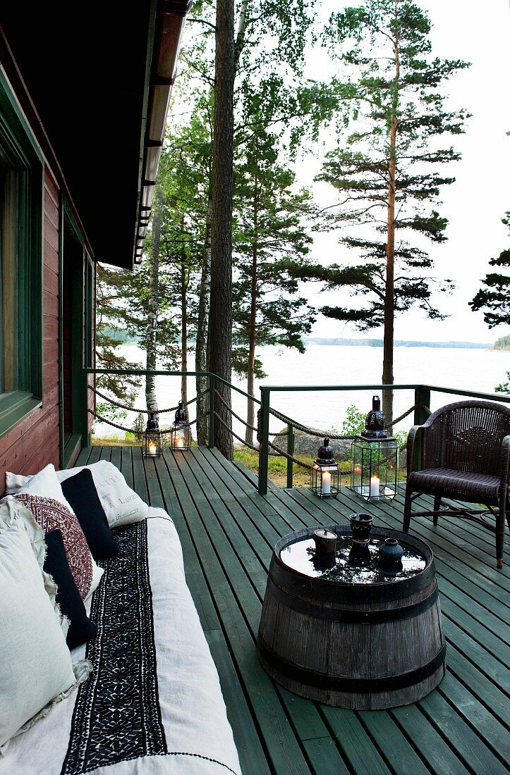 Wooden terrace with comfortable terrace furniture, candle arrangement and wonderful view of lake between tall pines and birches
