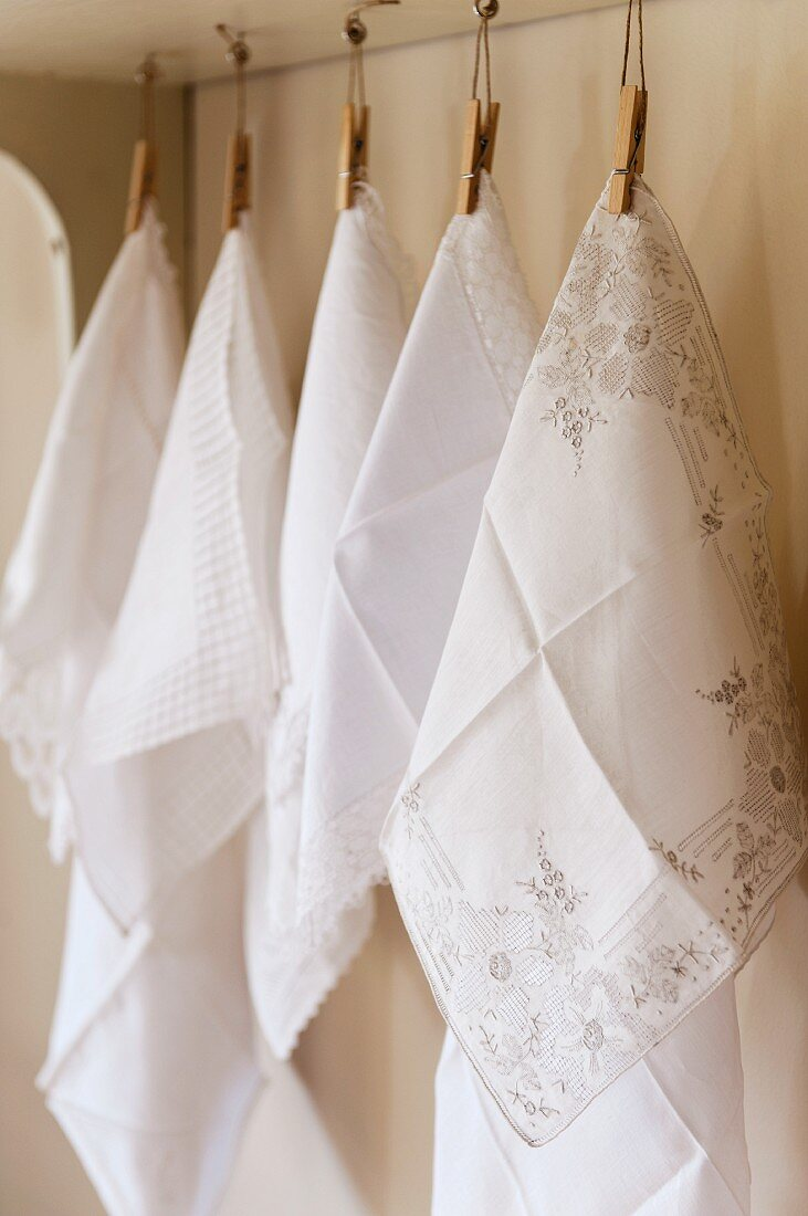 Fine embroidered white cotton hankerchiefs hung from wooden pegs