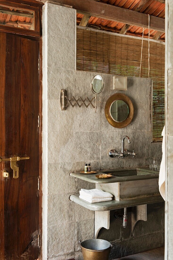 Stone washstand against wall of pale grey stone slabs and bamboo blind at window-like opening