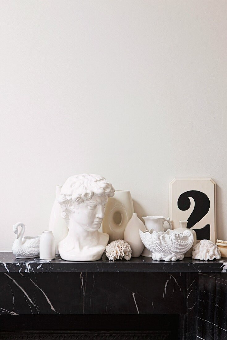 White ornaments such as a Greek bust, shells and vases on black marble mantlepiece