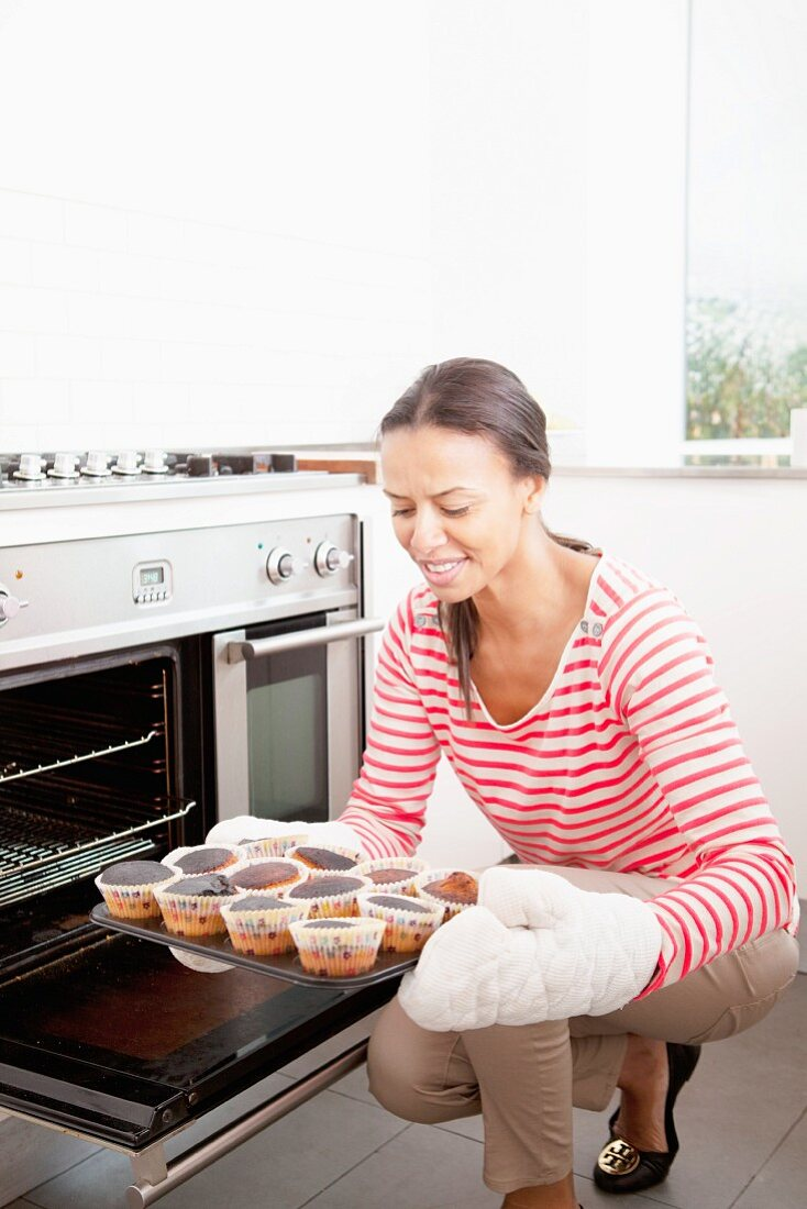 Woman holding a baking tray with burnt cupcakes