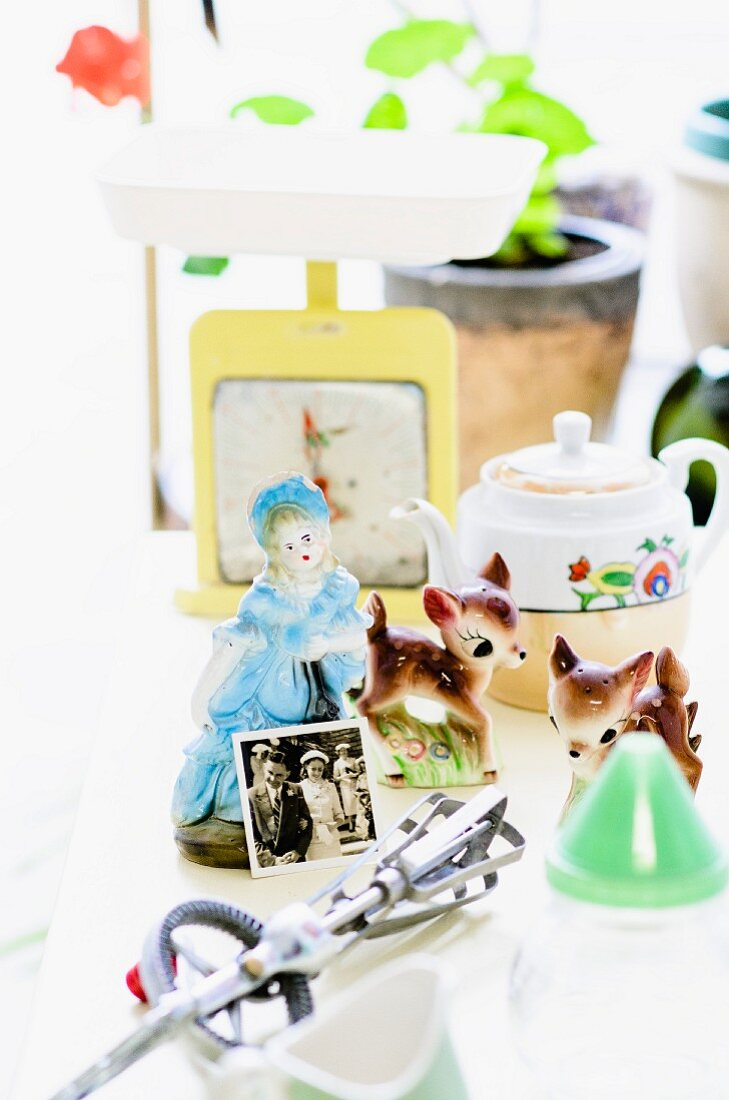Flea market finds - kitsch china figurines next to vintage hand whisk and various retro ornaments on table