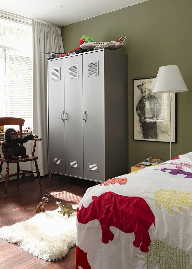 Kinderzimmer eines Jungen mit grauem Spind und einer gerahmten Zeichnung eines jungen Cowboys an der olivgrünen Wand, das Bett ist mit einer Tagesdecke abgedeckt
